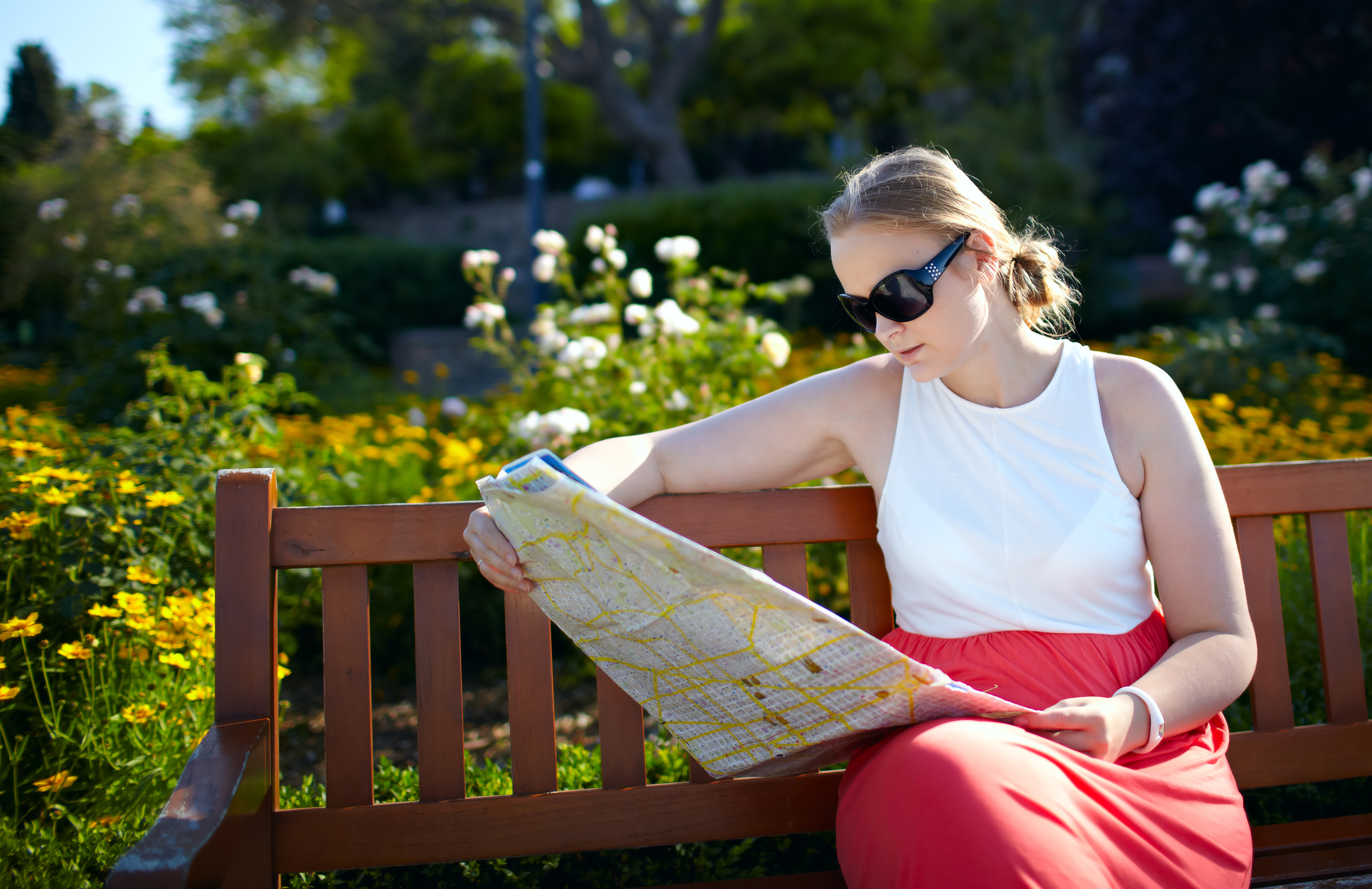 Young woman reading map on a bench in the park