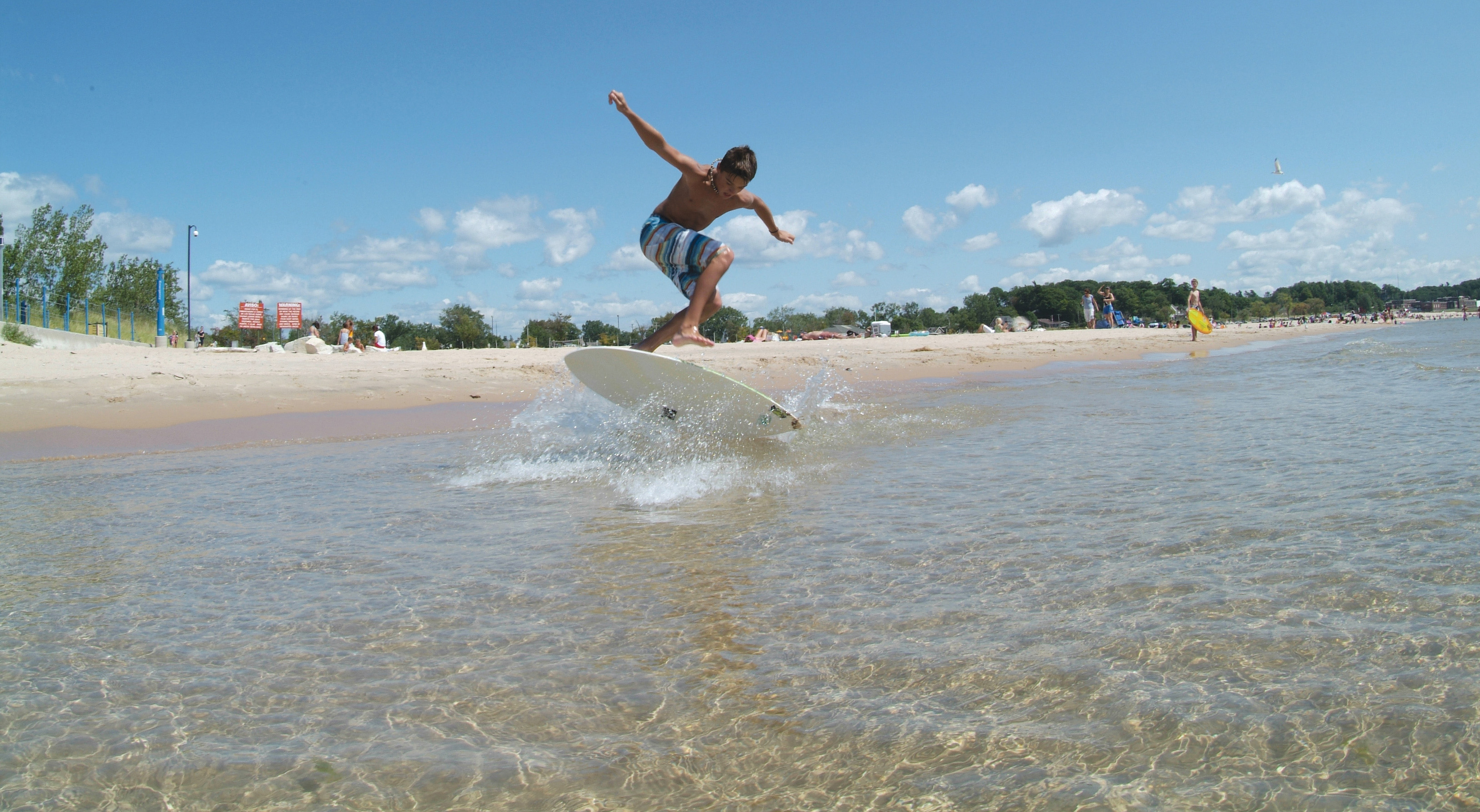Kid surfing by Lake Michigan shore