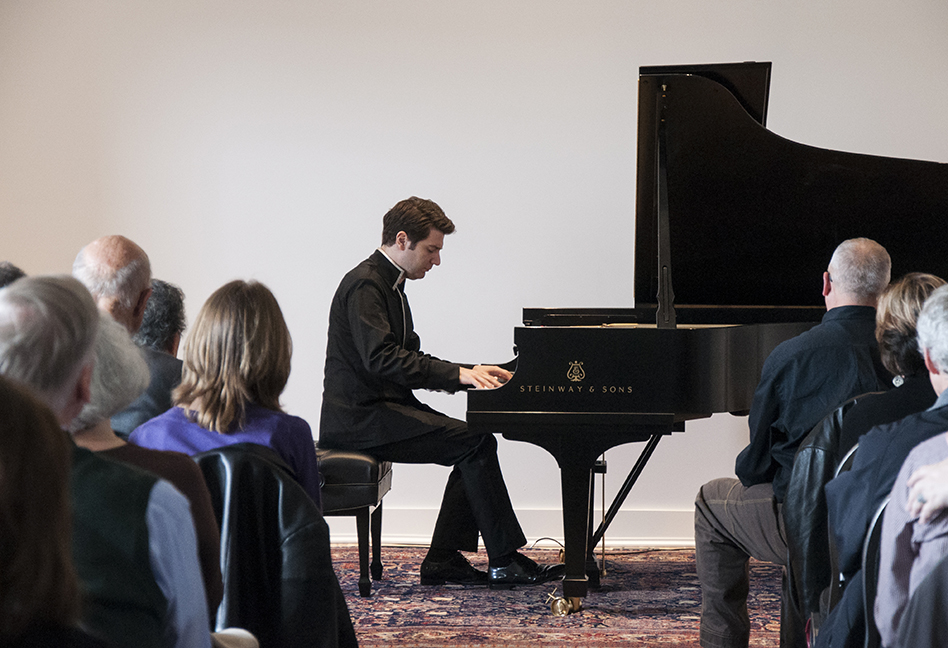 Alessio Bax playing piano for a group of people